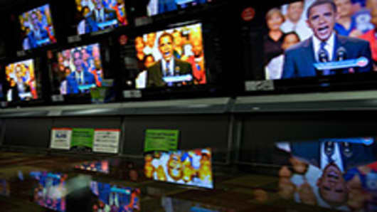 President Barack Obama is reflected on a glass table as he appears on television screens at an electronics shop in 2008 during a segment of a 30-minute prime-time infomercial.