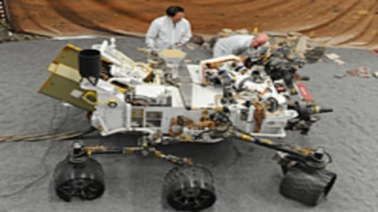 Jet Propulsion Laboratory (JPL) engineers James Wong (L) and Errin Dalshaug (R) examine a full size engineered model of the Mars rover Curiosity at JPL in Pasadena, California August 2, 2012.