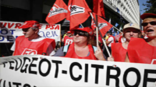 Protesters hold a banner during a demonstration of French car maker Peugeot PSA employees and unions against the planned layoffs and plant closing on July 25, 2012 in front of the PSA headquarters in Paris.