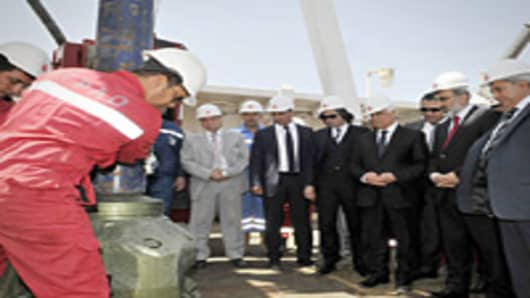 Turkey's Energy Minister (2R), Turkish Cypriot leader Dervis Eroglu (4R) and Turkish-Cypriot Prime Minister Irsen Kucuk (R), attend a ceremony an oil rig platform during a ground-breaking ceremony in the village of Sygkrasi, near Famagusta, where the state-run Turkish Petroleum Corporation (TPOA) bored their first onshore probe on April 26, 2012.Turkey began its first exploratory oil and gas drilling in the breakaway northern sector of the divided Cyprus on April 26, amid a dispute over rights t