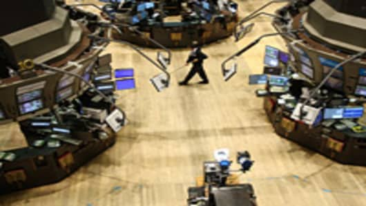 A janitor sweeps an empty trading floor at the New York Stock Exchange.