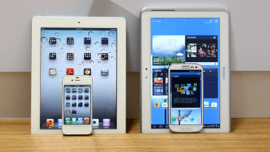 An Apple iPad 2 and iPhone 4S smartphone, left, and a Samsung Electronics Galaxy Tab 10.1 tablet computer and Galaxy S III smartphone.