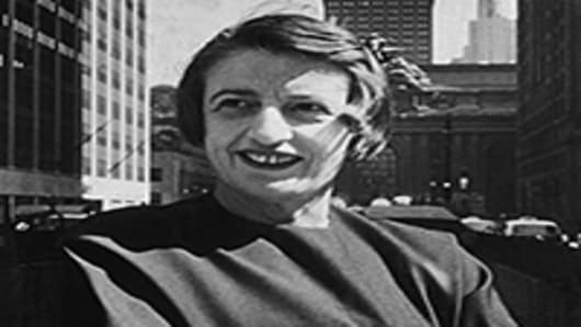 Russian-born American author and philosopher Ayn Rand, smiles and stands outdoors with her arms folded, in front of the Grand Central building, midtown Manhattan, New York City. 1957