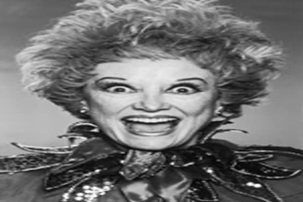 Headshot portrait of American comedian Phyllis Diller posing wide-eyed and openmouthed in an outfit with a sequined court jester's collar, circa 1984.