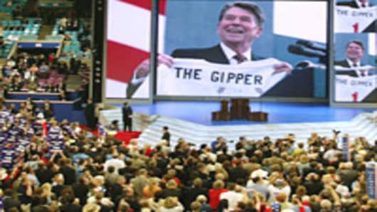 A video tribute shows an image of former President Ronald Reagan as people hold signs that say 'Win one for The Gipper' on the third day of the Republican National Convention in New York, September 1, 2004.