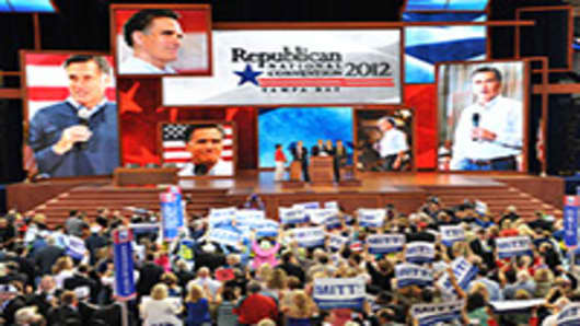 Delegates display signs in support of Mitt Romney following the tallying of votes during the roll call for nomination of president of the United States at the Tampa Bay Times Forum