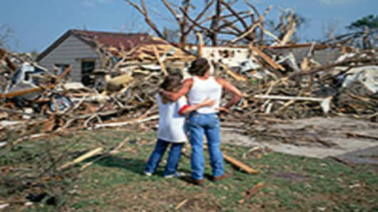 Couple looking at their home damaged by a tornado.