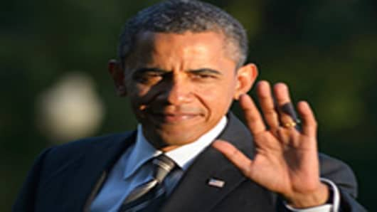 US President Barack Obama waves as he walks across the South Lawn upon return to the White House.
