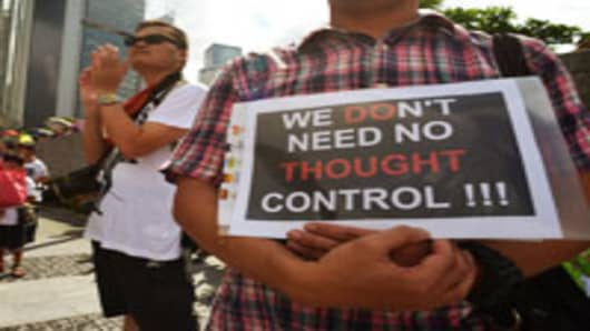 A man holding a placard reading 'we don't need no thought control' attends an anti Chinese patriotism classes protest outside of the government headquarters in Hong Kong.