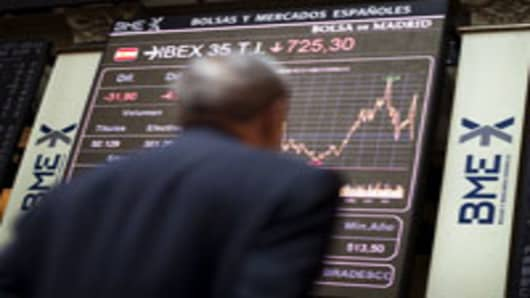 A trader looks at a display board showing information on the stock index, at the Madrid Stock Exchange in Madrid, Spain.