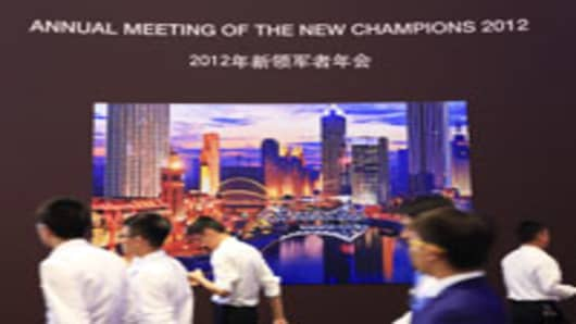 People walk past signage for the World Economic Forum Meeting of New Champions in Tianjin, China.
