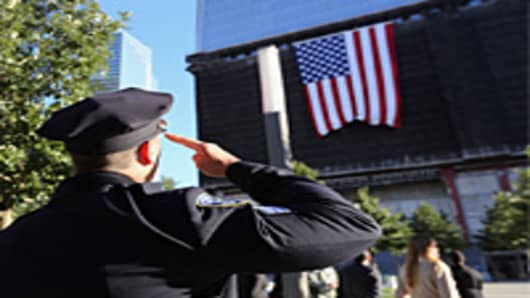 A New York City policeman salutes a flag hanging from One World Trade ceremonies for the eleventh anniversary of the terrorist attacks on lower Manhattan at the World Trade Center on September 11, 2012 in New York City.