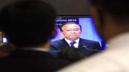 People watch an image presented on a television of Wen Jiabao, China's premier, speaking at the opening plenary session of the World Economic Forum (WEF) Annual Meeting of the New Champions in Tianjin, China, on Tuesday, Sept. 11, 2012.