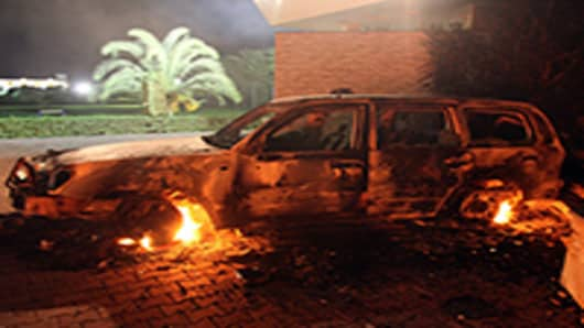 A vehicle sits smoldering in flames after being set on fire inside the US consulate compound in Benghazi late on September 11, 2012