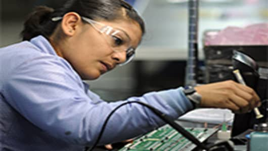 A worker solders components at the Suntron de Mexico assembly plant in Tijuana, Mexico.