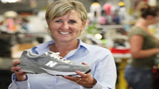 New Balance Plant Manager Raye Wentworth poses Tuesday, July 19, 2011 with a 993 athletic shoe at the New Balance shoe factory in Norridgewock, Maine.