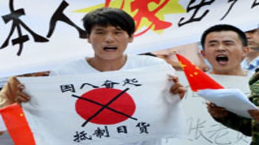 Anti-Japanese demonstrators hold banners and shout slogans as they protest over the Diaoyu Islands issue, known in Japan as the Senkaku Islands, outside the Japanese embassy in Beijing.