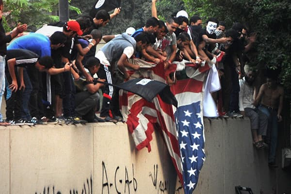 Thousands of anti-American protesters tear down the U.S. flag at the American Embassy in Cairo on Sept. 11, 2012, during a demonstration.