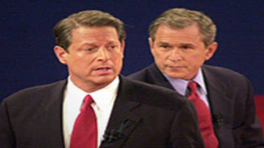 Democratic presidential candidate Vice President Al Gore talks to the audience while the Republican candidate Texas governor George W. Bush looks on October 17, 2000 in St. Louis, Missouri at the third and final presidential debate of the campaign.
