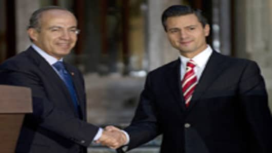 Mexican outgoing president Felipe Calderon (L) shakes hands with president elect Enrique Pena Nieto (R) after a private meeting at Los Pinos presidential residence on September 5, 2012 in Mexico City. Pena nieto said that he will try to mantain the country's stability avoiding to cut public policies of the presnt administration.