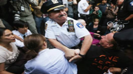 Protestors affiliated with Occupy Wall Street are arrested by NYPD officers while attempting to form a 'Peoples Wall' to block Wall Street on September 17, 2012 in New York City. Today is the one year anniversary of Occupy Wall Street and protestors are planning various actions and events throughout the day.