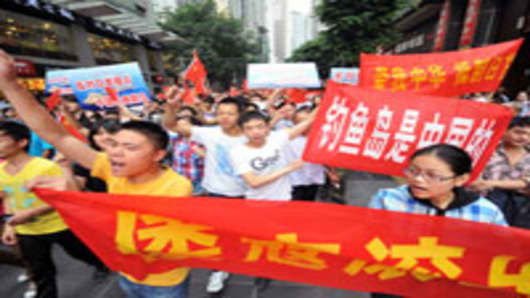 Chinese demonstraters carry anti-Japan banners and shout slogans during a protest over the Diaoyu islands issue, known as the Senkaku islands in Japan, in Chongqing, China.