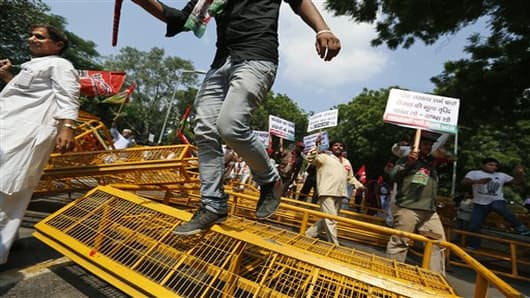 Activists of various left parties along with Samajwadi Party members jump over barricades as they try to get detained by police during a protest in New Delhi, India,Thursday, Sept. 20, 2012. Angry demonstrators disrupted trains Thursday and forced some shops and schools to close in a partly successful national strike protesting a government decision to cut fuel subsidies and open India's huge retail market to foreign companies. (AP Photo/Saurabh Das)