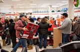 Black Friday shoppers wait to pay for items in a Sears store at Simon Property Group Inc.&#039;s Great Lakes Mall in Mentor, Ohio.