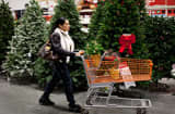 A shopper pushes a cart past a display of artificial Christmas trees at a Home Depot store.