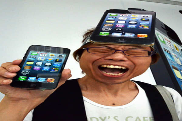 A customer reacts after purchasing Apple's new iPhone 5 smartphone at the Softbank mobile phone shop in Tokyo.