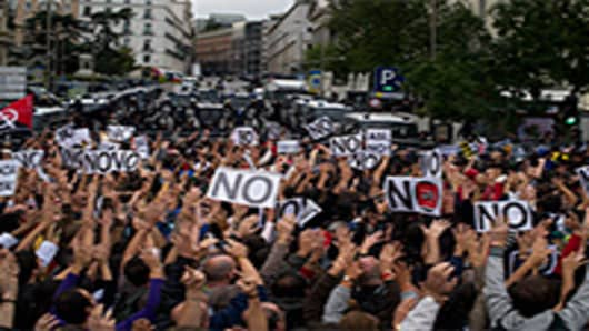 Demonstrators raise their hands in protest, while riot policemen wait at the other side of a fence blocking the acces to the Spanish parliament. Madrid, Spain