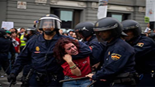 Riot policemen hold back a demonstrator during clashes around the Spanish parliament in a protest against spending cuts and the government of Mariano Rajoy. Madrid, Spain