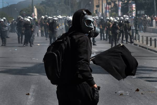 A demonstrator holds a black flag in front of riot police on September 26, 2012 in Athens during clashes with demonstrators on a 24-hour general strike. Police in Athens clashed with hooded youths mainly from anarchist groups (Zografou autonomous union)throwing firebombs on the sidelines of a large demonstration against a new round of austerity cuts.