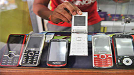 An Indian shopkeeper shows China Mobile phones in his mobile phone outlet in Hyderabad.