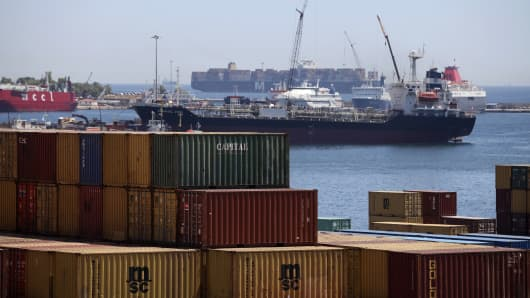 The Vemaoil XXIII cargo ship, center, sits moored beyond containers at the commercial terminal of Piraeus Port, operated by Piraeus Port Authority SA, in Athens, Greece, on Tuesday, June 12, 2012.