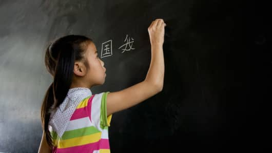 Chinese girl writing on chalkboard