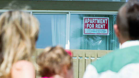 Family looks at apartment for rent sign