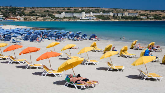 Malta, Mellietha Bay, Tourists sunbathing on beach.