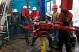 Floor hands and engineers adjust a down hole motor used for directional drilling on a natural gas drilling platform.