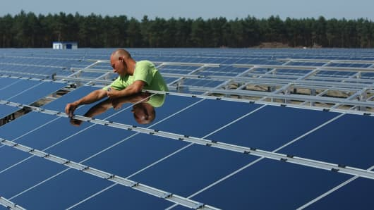 A worker installs solar panels at the Lieberose Solar Park on the park's partial inauguration day August 20, 2009 in Lieberose, Germany.