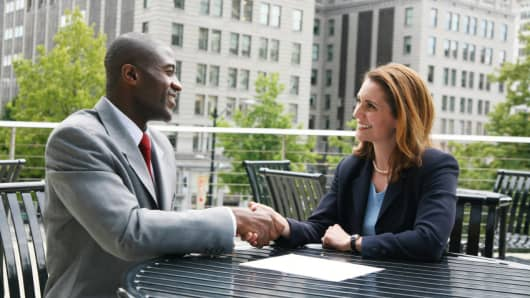 male and female shake hands at job interview