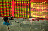 Investors watch the electronic board at a stock exchange hall in Hua