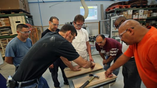 Instructor Doug Rappe, left, helps students participating in the woodworking manufacturing training program