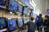 Consumers shop for televisions in Walmart.