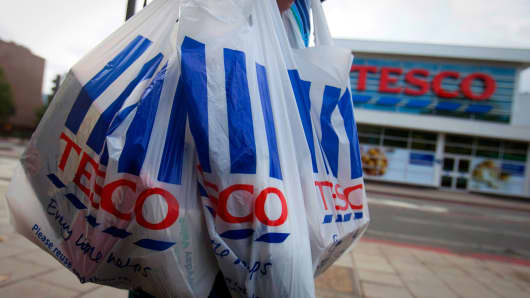 A customer carries Tesco-branded shopping bags as she leaves one of the company's stores.