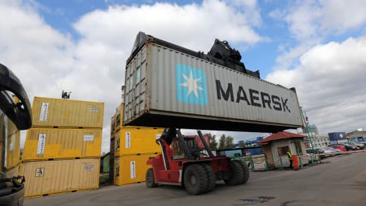 A worker drives a Kalmar reachstacker truck loaded with an AP Moeller-Maersk A/S shipping container.
