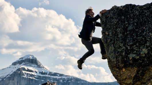 Businessman struggles to climb mountain summit.