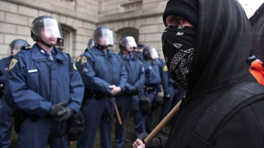 A masked protester looks at Michigan State Police in riot gear as union members from around the country rally at the State Capitol.
