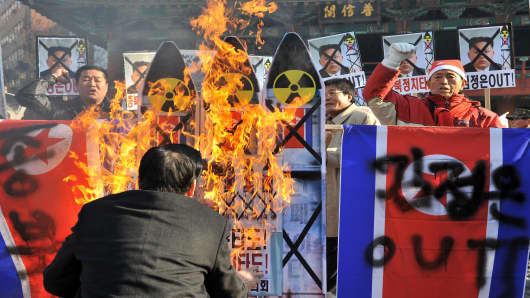 South Korean conservative activists burn anti-North Korean placards during a protest denouncing North Korea's rocket launch, in Seoul on December 12, 2012.