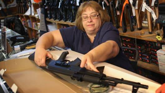 Cindy Sparr boxes up an AK-47 style rifle after selling it at Freddie Bear Sports sporting goods store.